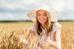 Mujer joven feliz en sombrero del sol en campo de cereal Foto de archivo libre de regalías