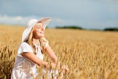 Mujer joven feliz en sombrero del sol en campo de cereal Imágenes de archivo libres de regalías