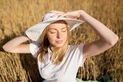 Mujer joven feliz en sombrero del sol en campo de cereal Imagen de archivo
