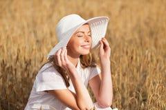 Mujer joven feliz en sombrero del sol en campo de cereal Fotos de archivo