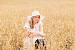 Mujer joven feliz en sombrero del sol en campo de cereal Foto de archivo