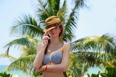 Mujer joven feliz en sombrero sobre fondo de la palmera exótica y del cielo azul Fotos de archivo