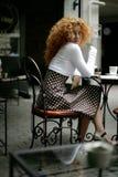 Mujer joven feliz en un café de la calle del estilo de París Imágenes de archivo libres de regalías