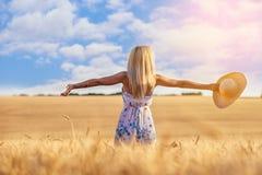 Mujer joven feliz en un campo de trigo Fotografía de archivo libre de regalías