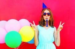 Mujer joven feliz en un casquillo del cumpleaños cerca de los globos coloridos de un aire Foto de archivo libre de regalías