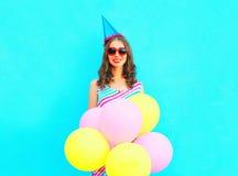 Mujer joven feliz en un casquillo del cumpleaños con los globos coloridos de un aire Imagen de archivo