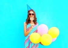 Mujer joven feliz en un casquillo del cumpleaños con los globos coloridos de un aire Imagenes de archivo