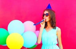 Mujer joven feliz en un casquillo del cumpleaños con los globos coloridos de un aire sobre fondo rosado Imagenes de archivo