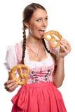 Mujer joven feliz en un dirndl que come los pretzeles foto de archivo