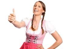 Mujer joven feliz en un donante del dirndl pulgares para arriba imagenes de archivo