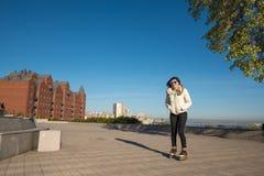 Mujer joven feliz en un patinaje sobre ruedas divertido de las gafas de sol en el PA Foto de archivo libre de regalías