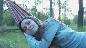 Mujer joven feliz en una hamaca La muchacha hermosa sonriente se relaja en la naturaleza, mintiendo en una hamaca metrajes