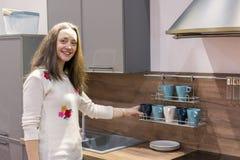 Mujer joven feliz en una nueva cocina moderna Mujer joven feliz con el pelo largo Fotos de archivo