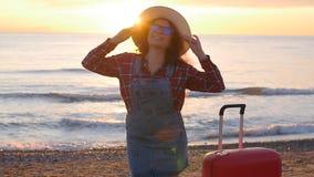 Mujer joven feliz en una playa de la puesta del sol almacen de video