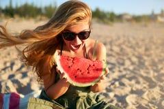Mujer joven feliz en vidrios que come la sandía en la playa arenosa de vacaciones Muchacha alegre que sostiene la sandía fresca fotos de archivo libres de regalías