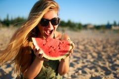 Mujer joven feliz en vidrios que come la sandía en la playa arenosa de vacaciones Muchacha alegre que sostiene la sandía fresca foto de archivo
