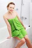 Mujer joven feliz envuelta en toalla después de baño Fotografía de archivo