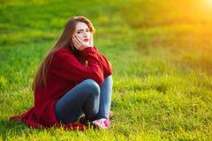 Mujer joven feliz Hembra hermosa con el pelo sano largo que disfruta de la luz del sol en el parque que se sienta en hierba verde Foto de archivo