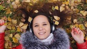 Mujer joven feliz hermosa con los auriculares que mienten en las hojas de otoño que escucha la música Estación, tecnología y gent Imágenes de archivo libres de regalías