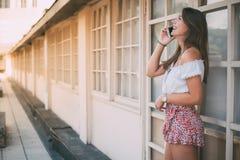 Mujer joven feliz hermosa en el teléfono móvil Fotografía de archivo