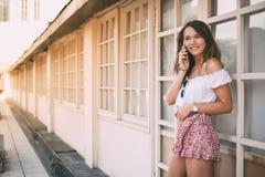 Mujer joven feliz hermosa en el teléfono móvil Imágenes de archivo libres de regalías