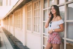 Mujer joven feliz hermosa en el teléfono móvil Imagenes de archivo