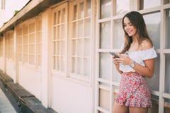 Mujer joven feliz hermosa en el teléfono móvil Fotos de archivo libres de regalías