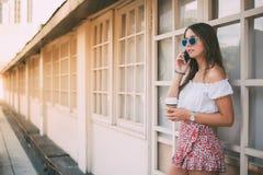 Mujer joven feliz hermosa en el teléfono móvil que bebe un coffe Imagen de archivo libre de regalías