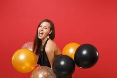 Mujer joven feliz hermosa en vestido negro que celebra sosteniendo los balones de aire aislados en fondo rojo ` S de la tarjeta d imagen de archivo libre de regalías