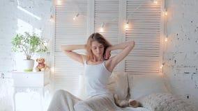 Mujer joven feliz hermosa que despierta por mañana y que estira en cama en casa almacen de metraje de vídeo