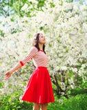 Mujer joven feliz hermosa que goza del olor en jardín floreciente de la primavera Imagen de archivo