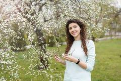 Mujer joven feliz hermosa que goza del olor en un jard?n floreciente de la primavera fotos de archivo libres de regalías