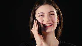 Mujer joven feliz hermosa que habla en el teléfono móvil aislado sobre negro metrajes