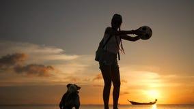 Mujer joven feliz hermosa que juega con el perro de Russell del enchufe en la playa durante puesta del sol asombrosa KOH Phangan, metrajes
