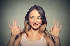 Mujer joven feliz hermosa que muestra la muestra aceptable con dos manos Fotos de archivo libres de regalías