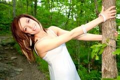 Mujer joven feliz hermosa que sostiene un árbol Foto de archivo libre de regalías