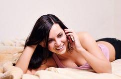 Mujer joven feliz hermosa que usa el cellphon Fotos de archivo