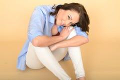 Mujer joven feliz hermosa Sat en el piso que se relaja Imagenes de archivo