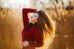 Mujer joven feliz libre Hembra hermosa con el pelo que sopla sano largo que disfruta de la luz del sol en parque en la puesta del Imagen de archivo libre de regalías