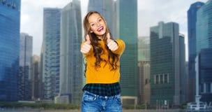 Mujer joven feliz o muchacha adolescente que muestra los pulgares para arriba Imagen de archivo libre de regalías