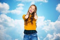 Mujer joven feliz o muchacha adolescente que muestra los pulgares para arriba Foto de archivo libre de regalías