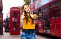 Mujer joven feliz o muchacha adolescente que muestra los pulgares para arriba Fotos de archivo