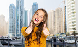 Mujer joven feliz o muchacha adolescente que muestra los pulgares para arriba Imagenes de archivo
