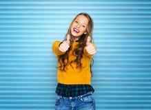 Mujer joven feliz o muchacha adolescente que muestra los pulgares para arriba Imágenes de archivo libres de regalías