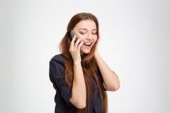 Mujer joven feliz preguntada que se coloca y que habla en el teléfono móvil Imagen de archivo libre de regalías