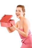 Mujer joven feliz que abre un rectángulo de regalo rojo Fotografía de archivo libre de regalías