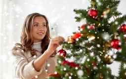 Mujer joven feliz que adorna el árbol de navidad Imagen de archivo