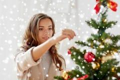 Mujer joven feliz que adorna el árbol de navidad Imagenes de archivo