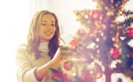 Mujer joven feliz que adorna el árbol de navidad Fotos de archivo libres de regalías