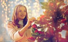 Mujer joven feliz que adorna el árbol de navidad Fotografía de archivo